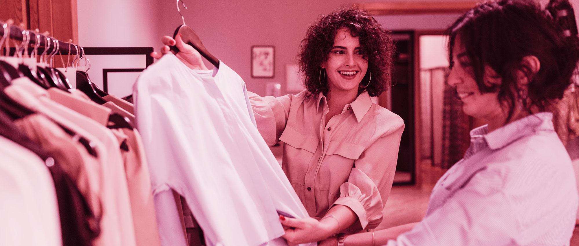 Sie sehen eine Szene aus dem Einzelhandel. Die eine Dame zeigt einer anderen eine schöne Bluse.